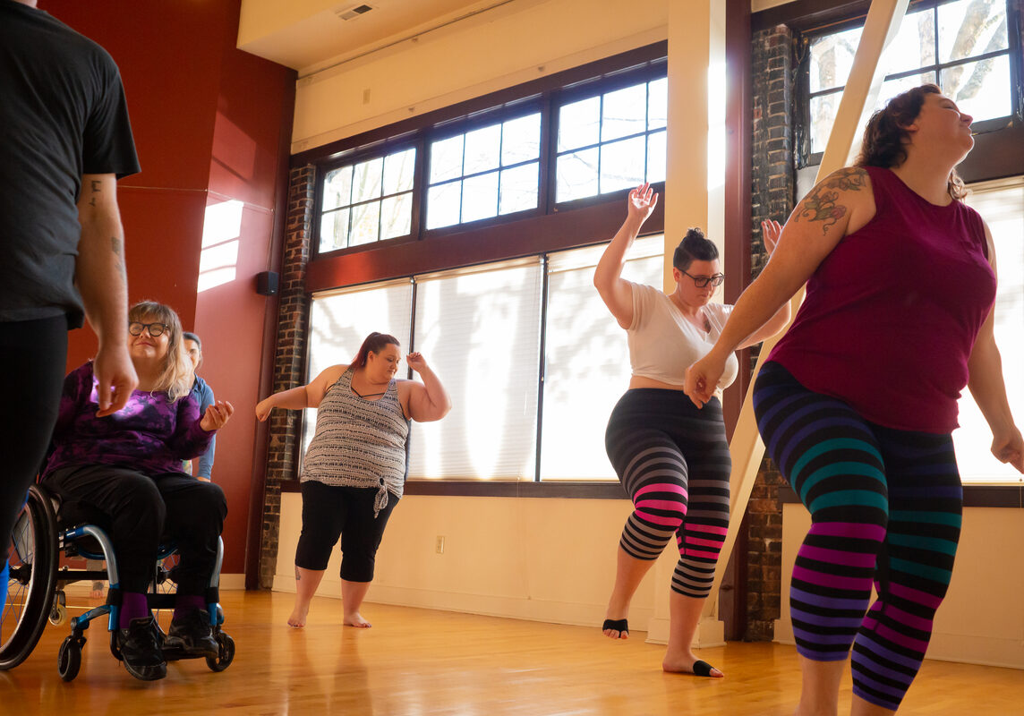 Students move, stretch, and dance in an inclusive dance class. The class includes people who are plus size or fat, people of color, and people with visible disabilities using mobility aids.